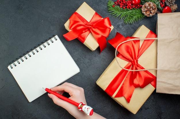 Acima, vista do clima de natal com belos presentes e cone de conífera de ramos de pinheiro ao lado do caderno com caneta em fundo escuro