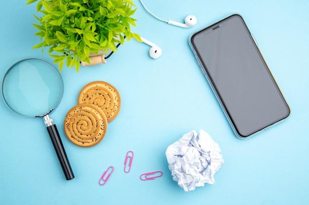 Acima, vista do conceito de escritório com fone de ouvido, celular, cookies de flores, lupa de papel esmagado na superfície azul