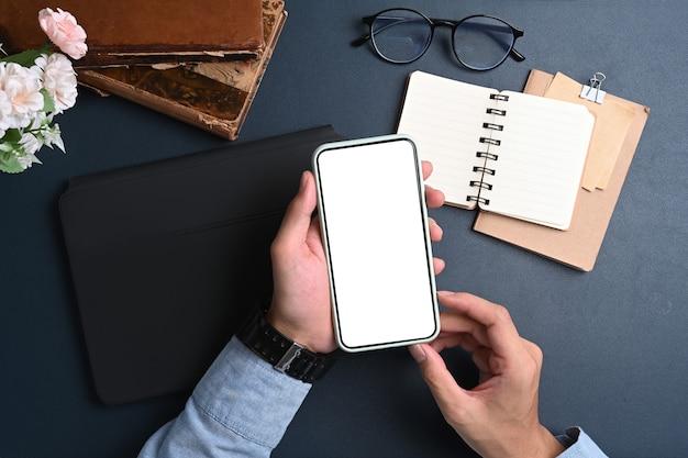 Acima, vista do empresário segurando simulado um telefone móvel com tela vazia sobre a superfície azul escura.