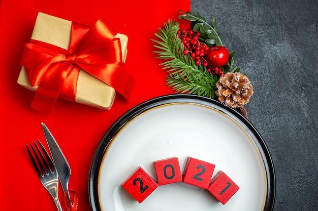 Acima, vista do fundo de ano novo com números em talheres de prato de jantar conjunto de acessórios de decoração ramos de abeto ao lado de um presente em um guardanapo vermelho