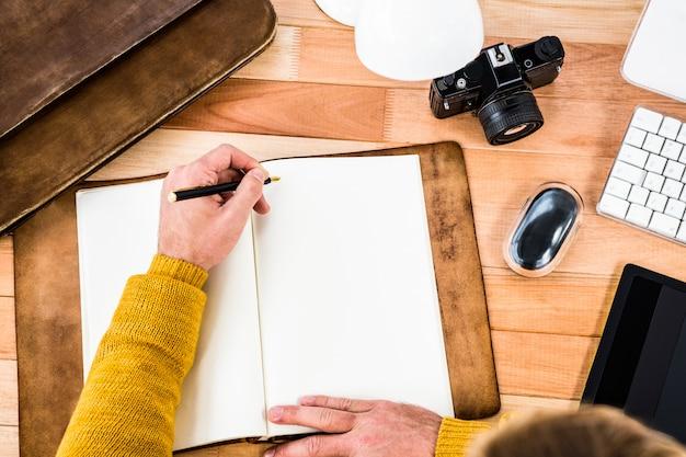Acima vista do homem escrevendo no notebook na mesa de madeira