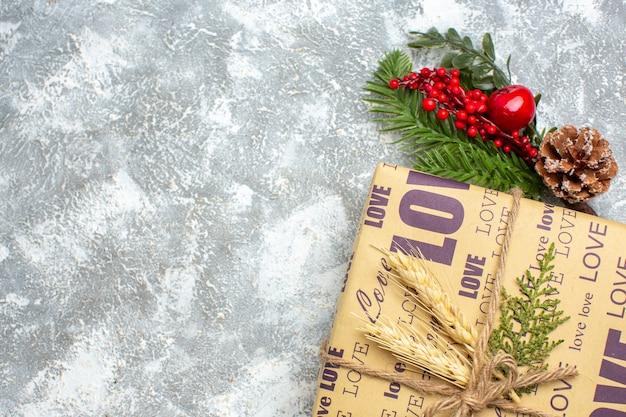 Acima, vista do lindo presente embalado de natal com inscrição de amor e acessórios de decoração de ramos de pinheiro cone de conífera na superfície do gelo