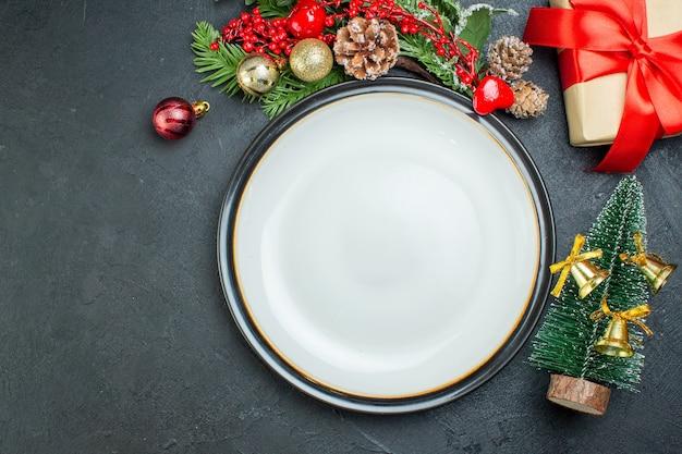 Acima, vista do prato de jantar, árvore de natal, ramos de abeto, coníferas, caixa de presente no lado esquerdo em fundo preto
