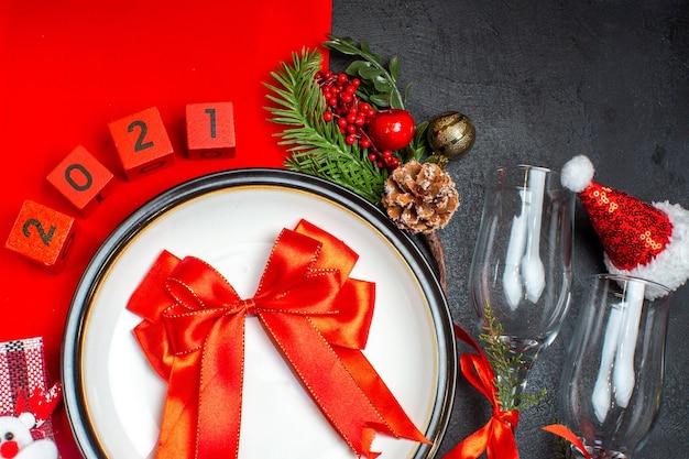 Acima, vista do presente com fita vermelha acessórios de decoração de pratos de jantar ramos de abeto xsmas taças de vidro chapéu de papai noel na mesa escura