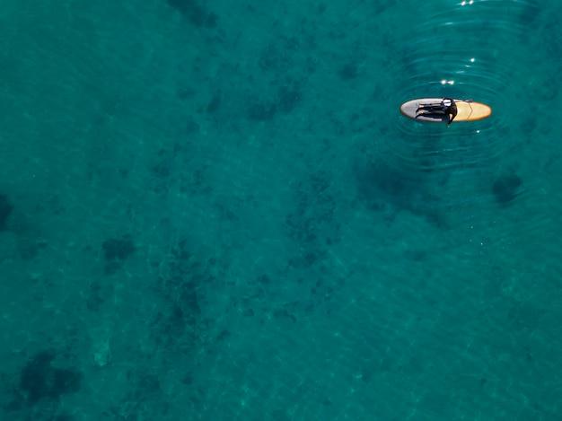 Acima, vista, homem deitado na prancha de surf
