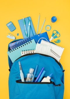 Acima vista mochila com material escolar