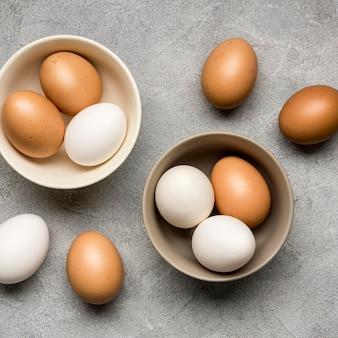 Acima vista tigelas com ovos de galinha