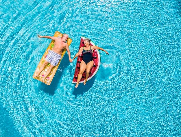 Acima, vista vertical de pessoas idosas casal de idosos pegando as mãos com amor e se divertindo na piscina azul claro juntos aproveitando as férias de verão com colchão inflável da moda