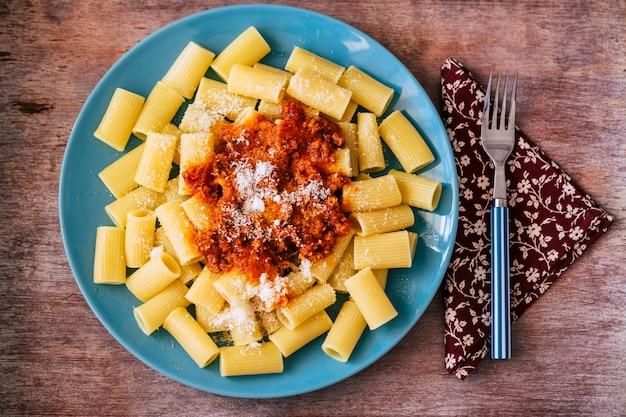 Acima, vista vertical superior de comida de massa italiana com molho de tomate ou bolonhesa - restaurante ou momento de jantar em casa