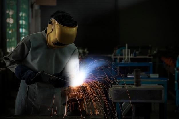 Aço de solda de trabalho do soldador do trabalhador na indústria com as luvas da máscara da segurança e o equipamento de segurança.