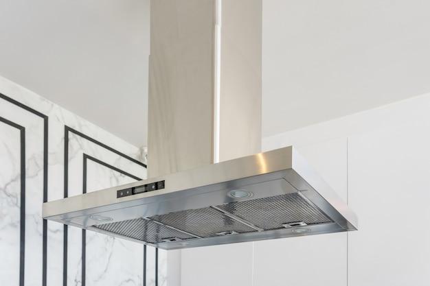 Aço inoxidável moderno e exaustor no interior da cozinha.