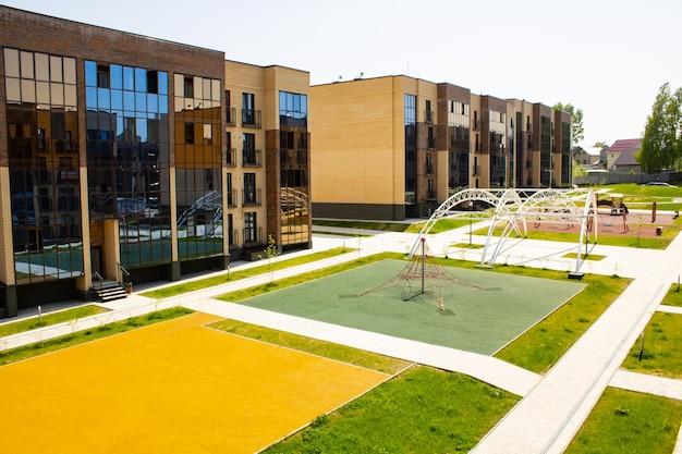 Acolhedor complexo residencial de edifícios de tijolos de vários andares e um playground. paisagem da cidade. prédios baixos com pátio para atividades de lazer.