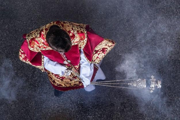 Acólito da igreja católica equilibrando um incentivo. almas purificadoras.