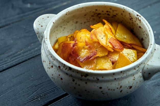 Acompanhamento apetitoso - batatas fritas com cebola servidas em uma tigela branca sobre uma superfície escura.