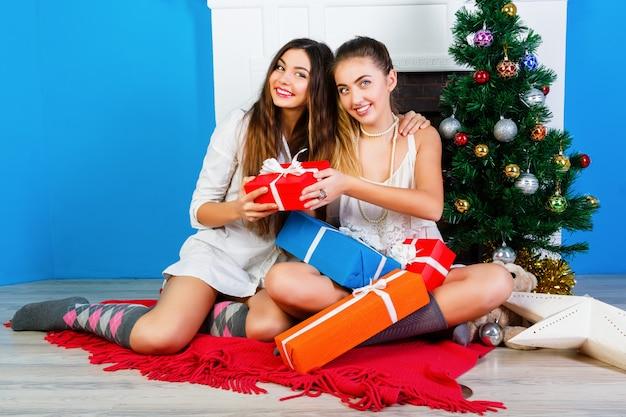 Aconchegante brilhante murchar o retrato do feriado de duas irmãs bonitas de duas melhores amigas, sentadas perto da lareira e decorada a árvore de natal e segurando presentes de sua família. emoções positivas e humor.