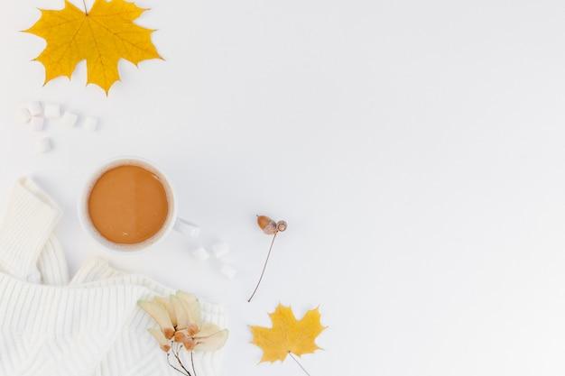 Aconchegante camisola branca quente e humor de copo de café outono e fundo branco