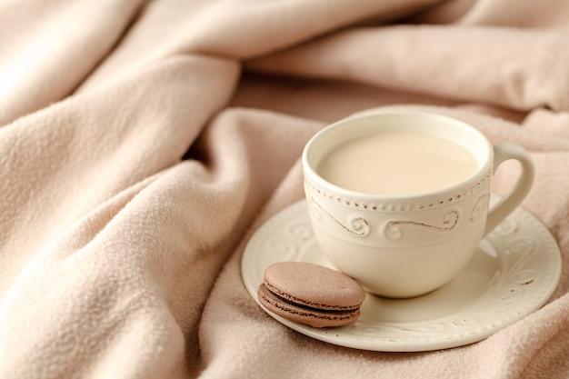 Aconchegante casa fundo de inverno, xícara de café quente com leite, camisola de malha quente sobre fundo branco da cama, tom vintage. conceito de estilo de vida