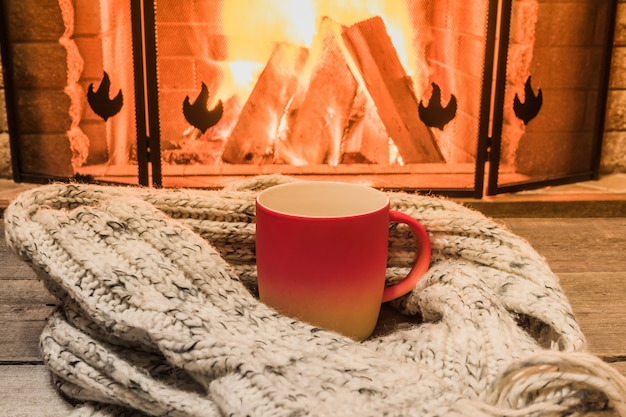Aconchegante cena perto da lareira com um copo vermelho com chá quente e aconchegante cachecol quente.