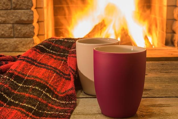 Aconchegante cena perto da lareira com xícaras de chá quente e aconchegante cachecol quente.