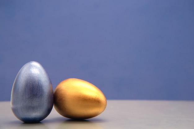 Aconchegante conjunto de ovos de páscoa de azul e prata sobre fundo azul.