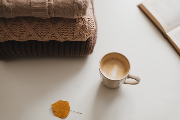Aconchegante e confortável atmosfera caseira de inverno e outono e natureza morta com um livro de copas e suéteres quentes