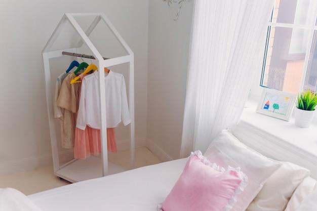 Aconchegante e espaçosa sala de luz com roupas da moda em cabides, cama confortável com quarto branco