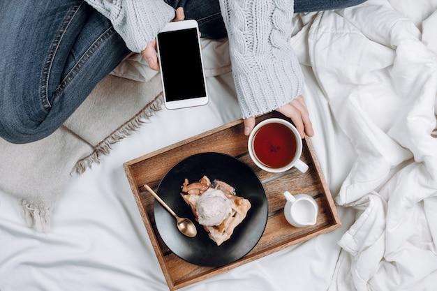 Aconchegante flatlay de cama com bandeja de madeira com torta de maçã vegana, sorvete e chá preto e mulher de jeans e suéter cinza segurando o smartphone com copyspace preto em lençóis e cobertores brancos