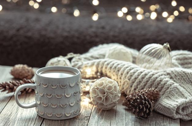 Aconchegante fundo de natal com uma bela xícara e detalhes de decoração em um fundo desfocado com bokeh.