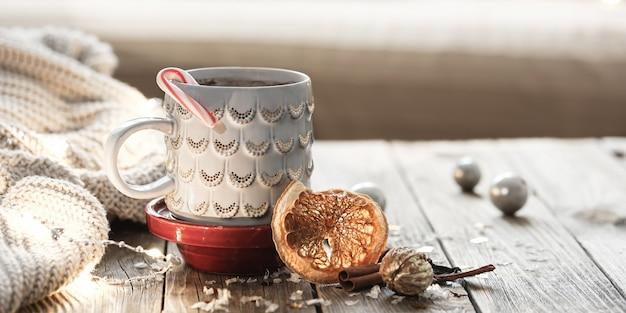 Aconchegante fundo de natal com uma xícara, elemento de malha, clima de inverno, conforto do lar.