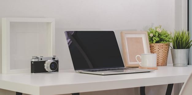 Aconchegante home-office com laptop de tela em branco aberto com câmera vintage e material de escritório