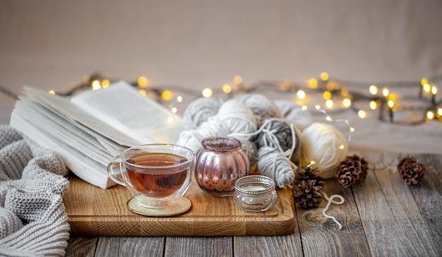 Aconchegante natureza morta com chá e itens decorativos, luzes brilhantes ao fundo.