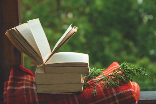 Aconchegante natureza morta de outono: xícara de café quente e livro aberto no parapeito da janela vintage com manta vermelha, abóbora, pinha, velas e chuva lá fora. outono. apartamento. chuva