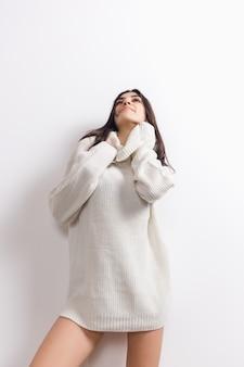 Aconchegante. retrato de uma linda mulher morena de manga comprida macia confortável isolada na parede branca. conforto doméstico, emoções, expressão facial, conceito de clima de inverno. copyspace.