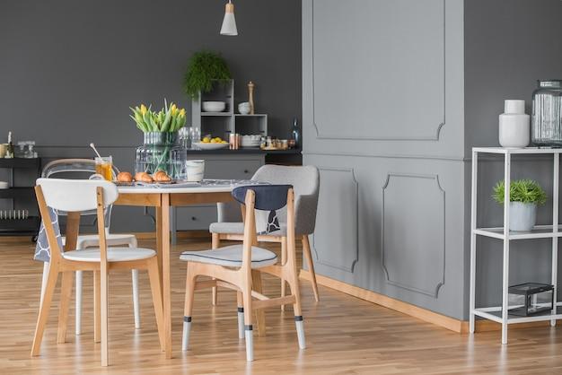 Aconchegante sala de jantar cinza no interior da cozinha com mesa, cadeiras e piso de madeira