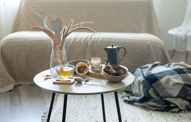 Aconchegante vida em casa com uma xícara de chá, abóboras, velas e detalhes de decoração de outono em uma mesa sobre um fundo desfocado.