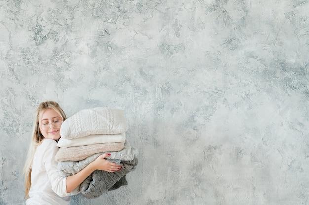 Aconchego e conforto do lar. dona de casa encantada com cobertor de tricô quente e pilha de travesseiro.