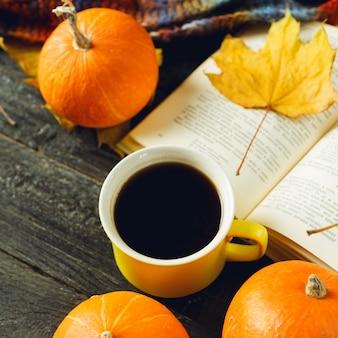 Aconchego outono. uma xícara de café, um livro, pequenas abóboras e folhas de outono brilhantes