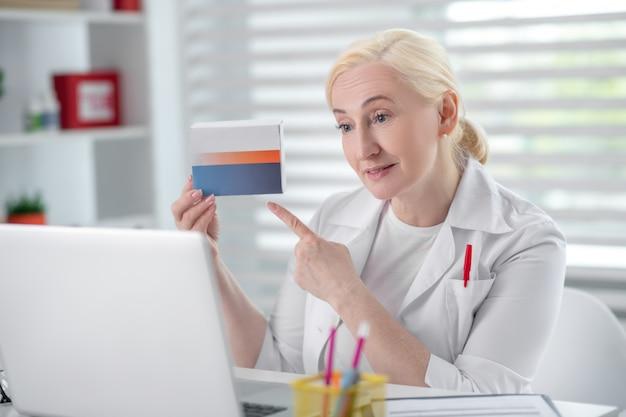 Aconselhamento online, medicina. mulher bonita bem sucedida no jaleco branco, segurando a caixa do medicamento na frente da tela do laptop, consultoria on-line.