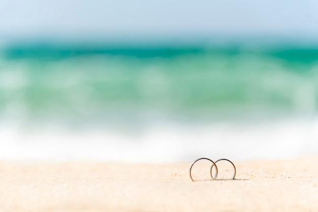 Acople as alianças de casamento na praia tropical da areia do verão com espaço da cópia. design de exibição para o conceito de agência de viagens de lua de mel. anéis de casamento na areia com férias de casal para propor casamento