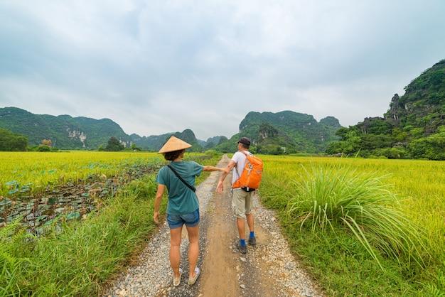 Acople o passeio em conjunto na estrada entre campos do arroz. homem com mochila e mulher com chapéu vietnamita se divertindo, ninh binh vietnam