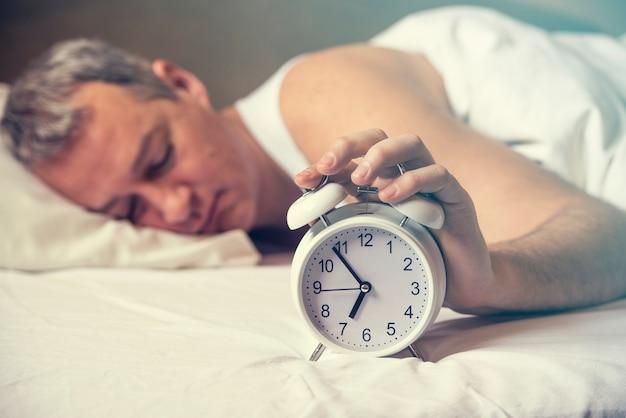 Acordado. a mão desliga o despertador que acorda de manhã. tom de pele suave. homem esgotado sendo despertado por um despertador em seu quarto