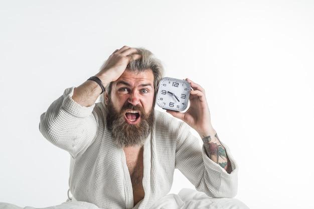 Acordando tarde do prazo, homem com despertador homem barbudo na cama, manhã manhã, despertador de rotina