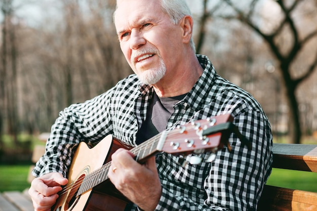 Acorde básico. homem maduro inspirado posando no parque e tocando violão