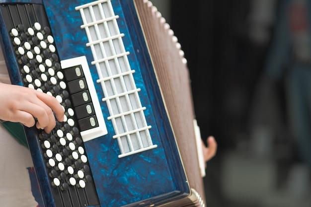 Acordeão nas mãos de um músico, close-up vista. imagem de música de rua, busker tocando um melodeon
