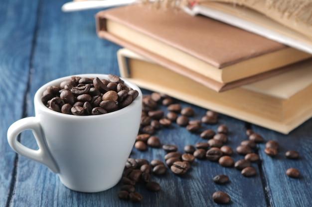 Acordo com grãos de café em uma xícara e livros sobre uma mesa de madeira azul.
