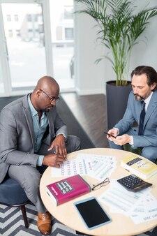 Acordo de assinatura. vista superior de empresário de pele escura assinando acordo com parceiro de negócios