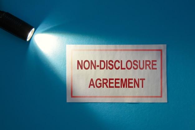 Acordo de não divulgação - inscrição em um cartão branco no feixe de luz