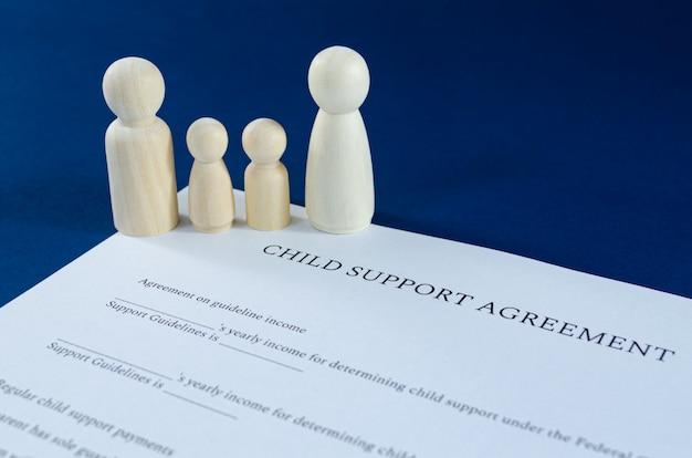 Acordo de pensão alimentícia impresso com figuras de madeira de homem, mulher e crianças em uma imagem conceitual para pensão financeira. sobre o espaço azul.