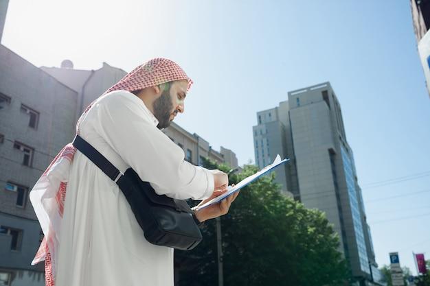 Acordo. retrato do homem árabe rico durante a compra de imóveis, centro de negócios na cidade. etnia, cultura. homem confiante com roupas tradicionais, tornando um negócio bem-sucedido. finanças, economia.