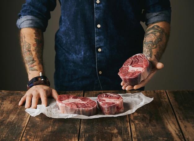 Açougueiro brutal com mãos tatuadas oferece um pedaço de grande bife de carne crua na câmera, outros bifes em papel ofício branco na mesa de grunge de madeira velha vintage. irreconhecível